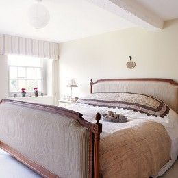 Cream country bedroom with upholstered bed