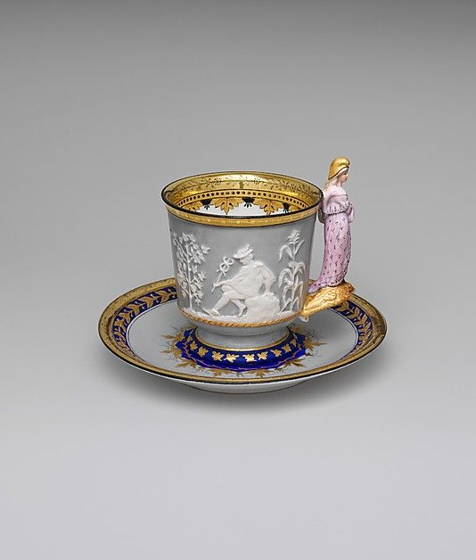 The Liberty Cup and Saucer, by Union Porcelain Works, 1876. Made for display at the Centennial Exhibition, this porcelain cup and saucer are decorated with both classical and patriotic designs. The handle consists of a figure of Liberty standing on the back of an American eagle.