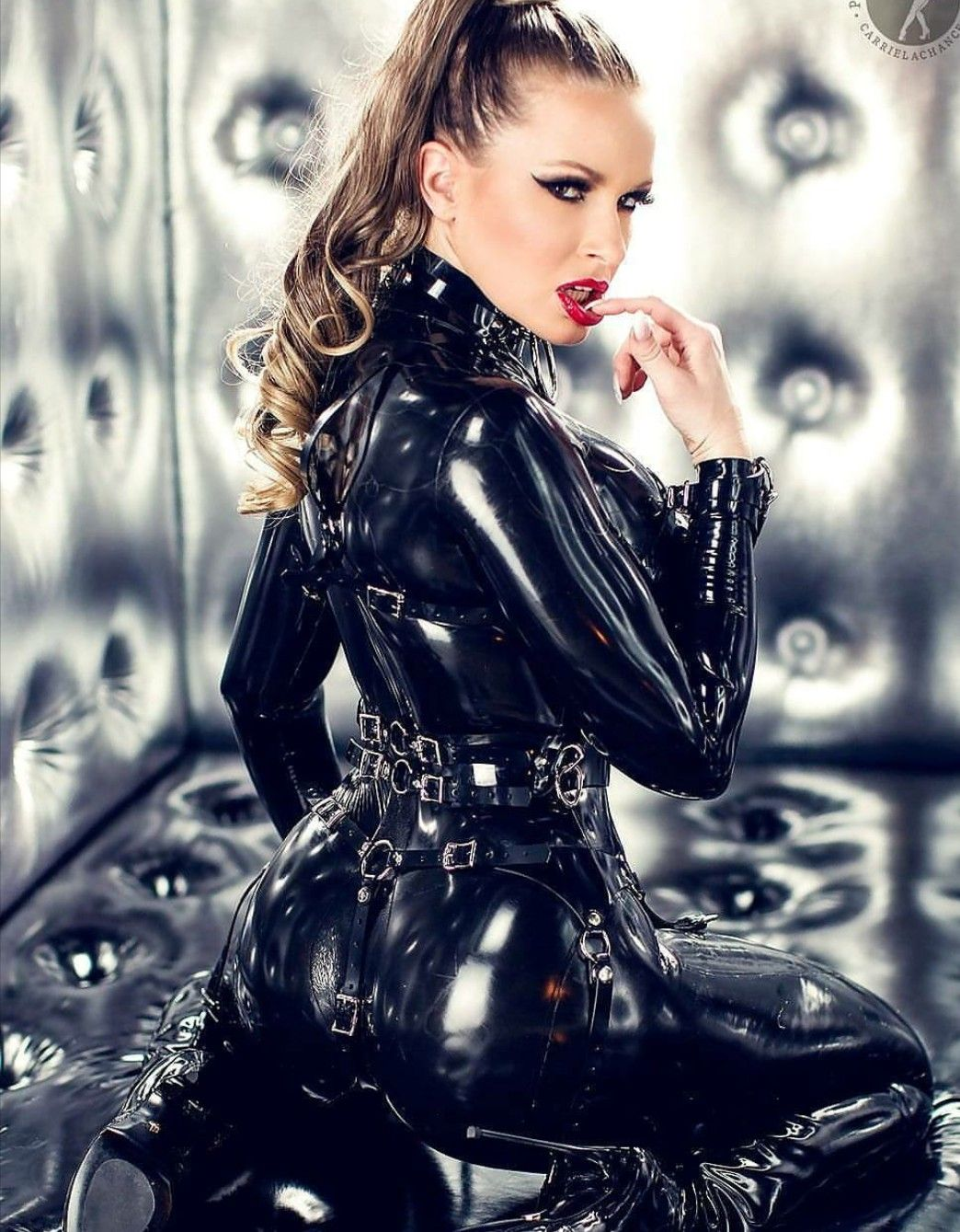 Carrie LeChance black latex catsuit with harnesses.  7c4c5385b8