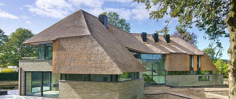 Grote villa grote glaspartijen laag doorlopend rietendak langwerpige bouwstenen modern for Modern huis binnenhuisarchitectuur villas