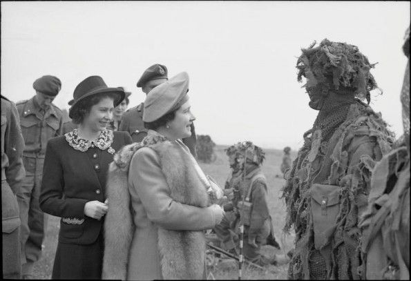 MAY 19 1944 British 6th Airborne are ready for Normandy The Queen and Princess Elizabeth talk to a camouflaged sniper during a tour of Airborne forces, 19 May 1944.
