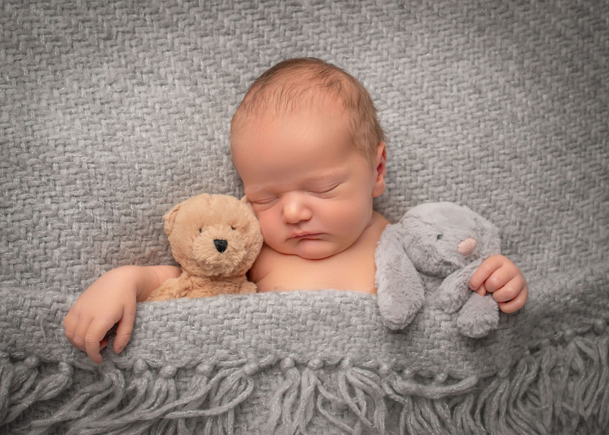Newborn baby sleeping under grey blanket with two stuffed animals #babykidclothesandideas