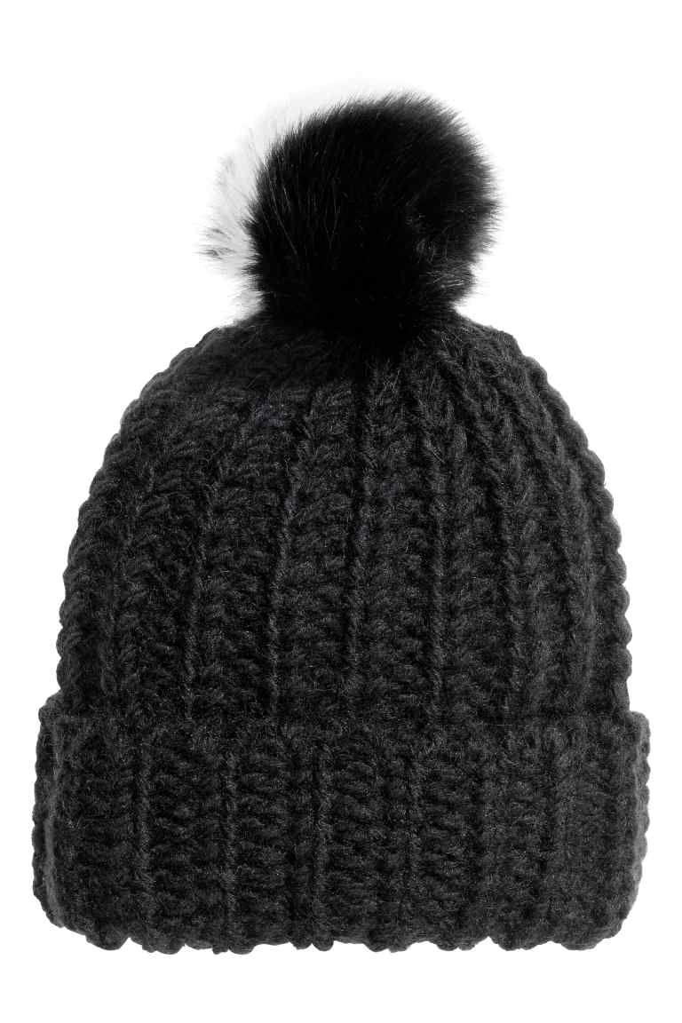 baa8509fb35bd Gorro con pompón  Gorro en punto de canalé suave con lana en la trama. Pompón  de pelo sintético en la parte superior.