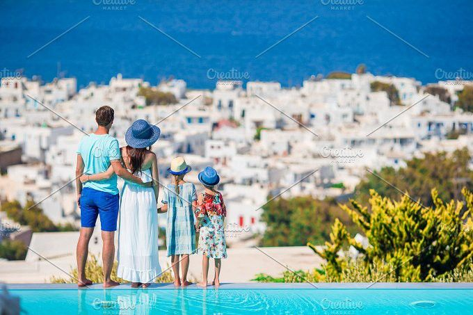 Parents and kids on outdoor swimming pool background Mykonos town on Cyclades, Greece. People Photos. $9.00
