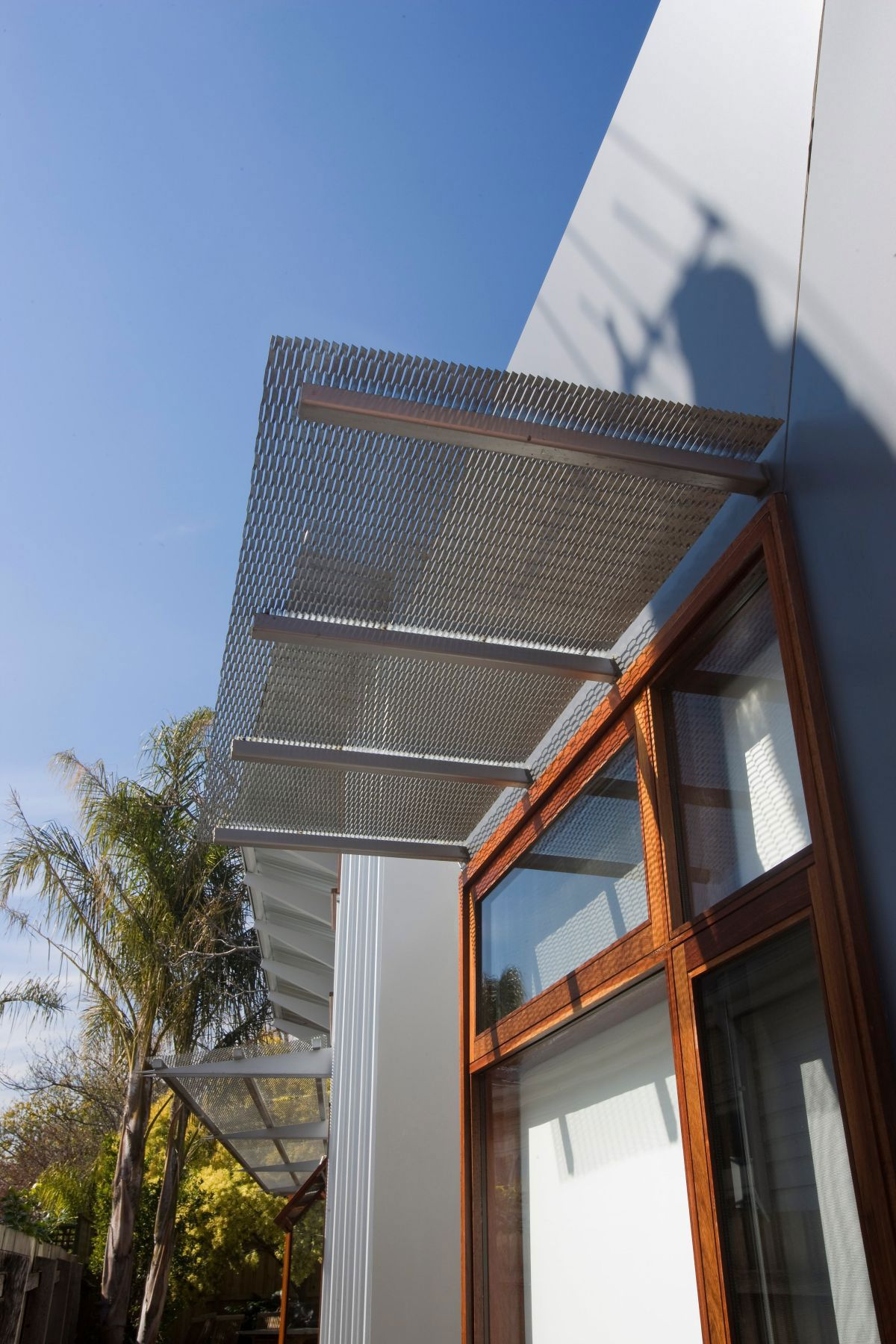 Modern Single House Design With Steel Mesh Awnings And Wooden