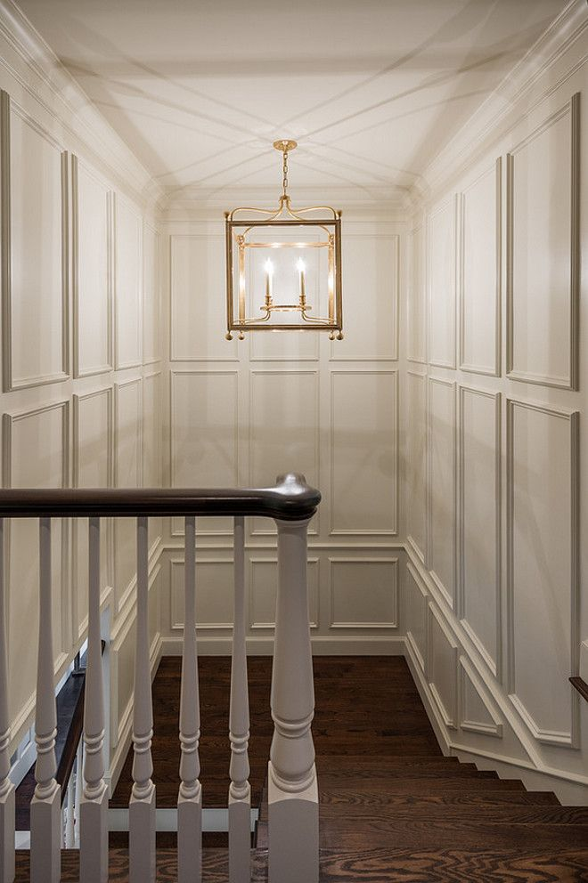 stairway lighting stairway featuring paneled walls and lantern