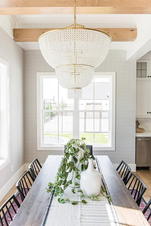 A Aerin Two Tier Jacqueline Chandelier Hangs From A Ceiling Accented With Chunk Wood Beams Over