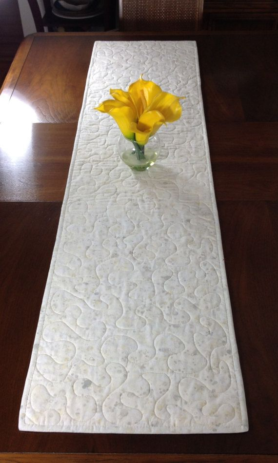 Although designed as a modern look table runner, this quilt could also be used to adorn your wall, a dresser, coffee table, sofa table, buffet, desk, bed or piano top. The green and cream color scheme is versatile and can be used in any season. A layer of batting enclosed between two layers