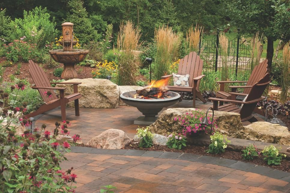 This Enchanting Paver Patio Features A Pathway Around A Natural Stone Pond A Sunken Fire Pit Space Surrounded By Brown Ad Rustic Landscaping Paver Patio Patio