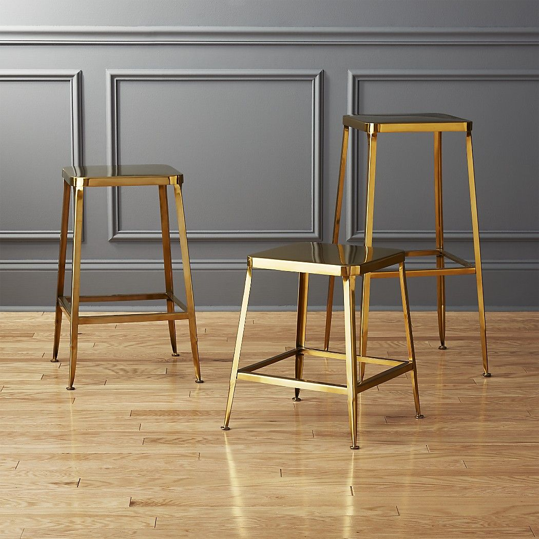 Shop flint gold bar stools.   Factory-inspired stool parks square at the bar in flint steel with a glam gold finish and exposed welding.  Legs flare refined, love those little capped feet.  Each a handcrafted original.