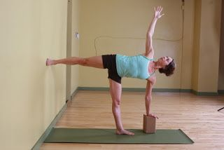 yoga modified pose halfmoon with foot against a wall and