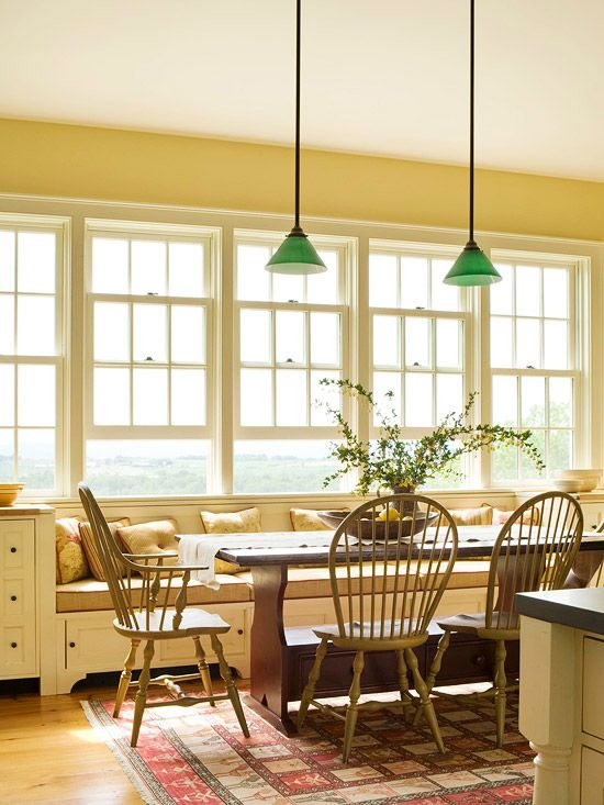 A bench beneath a bank of windows looks lovely in this cozy country kitchen.