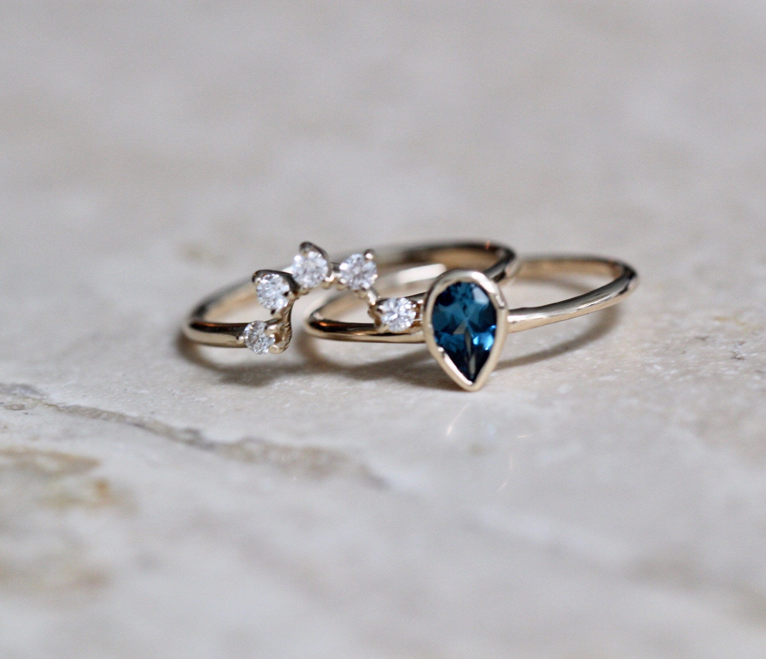 This wedding set features a gorgeous pear-shaped London Blue Topaz which nestles perfectly with a curved band crowned with diamonds. Perfect for the off-beat bride looking for something a little more special! - London Blue Topaz measures 6mm by 4mm - Diamonds each measure 2mm (.15 Ct total), conflict free - Round band measures 1.3mm - Handcrafted out of 14K yellow, rose or white gold - Please convo us directly for different center stone options Processing times - Current processing time is 1 - 3