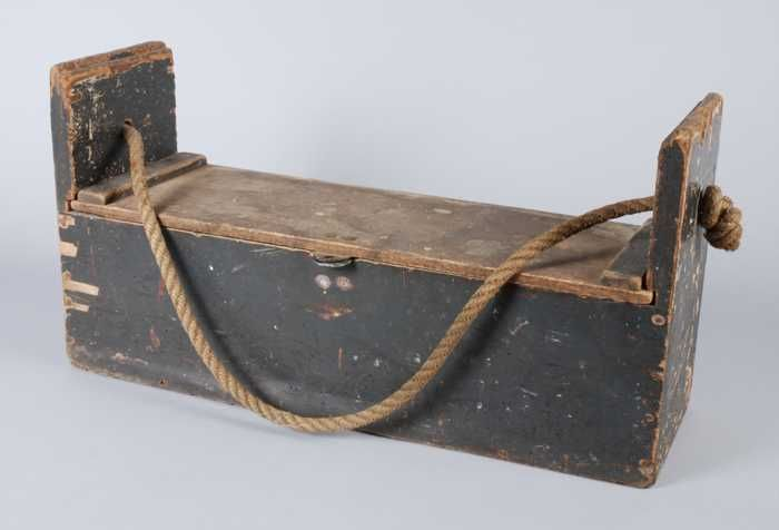 Dark painted carpentry box with sliding lid, filled with various tools