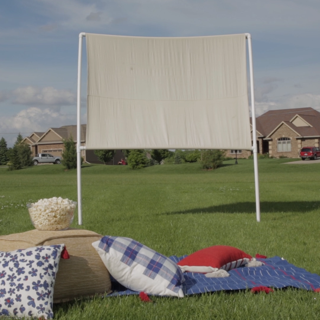 PVC pipes and a drop cloth come together to make all your summer movie-night dreams come true. Turn your backyard into your own personal theater with this easy DIY movie screen. #outdoortheater #laborday #outdooractivity #movienight #diyoutdoormoviescreen #bhg