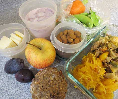 Apple, plums, cheese slices, muffin, leftover dinner, almonds, vegetables, and yogurt in containers.