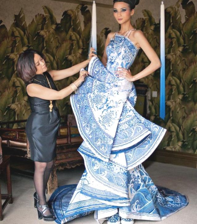 China's Fashion Couture Designer, Guo Pei primping a model backstage.  {amazing creation:  Blue & White Chinoiserie Porcelain inspired blue gown}
