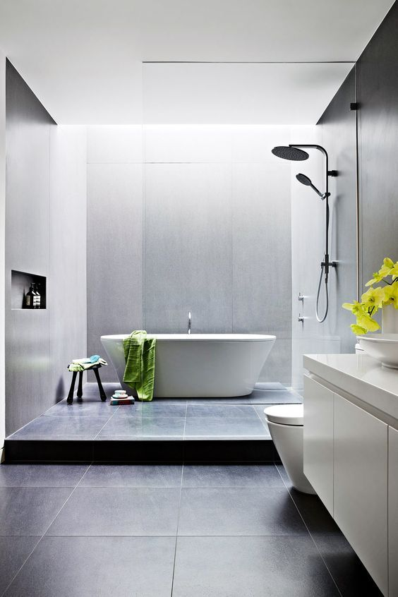 a clean modern space with grey and black tiles a free standing tub