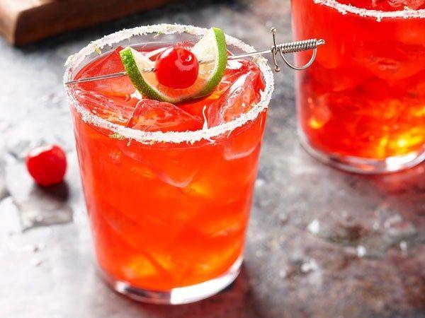 Cherry-Lime Margaritas #limemargarita Sugar-rimmed glass filled with cherry-lime margarita, garnished with lime slice and maraschino cherry #limemargarita