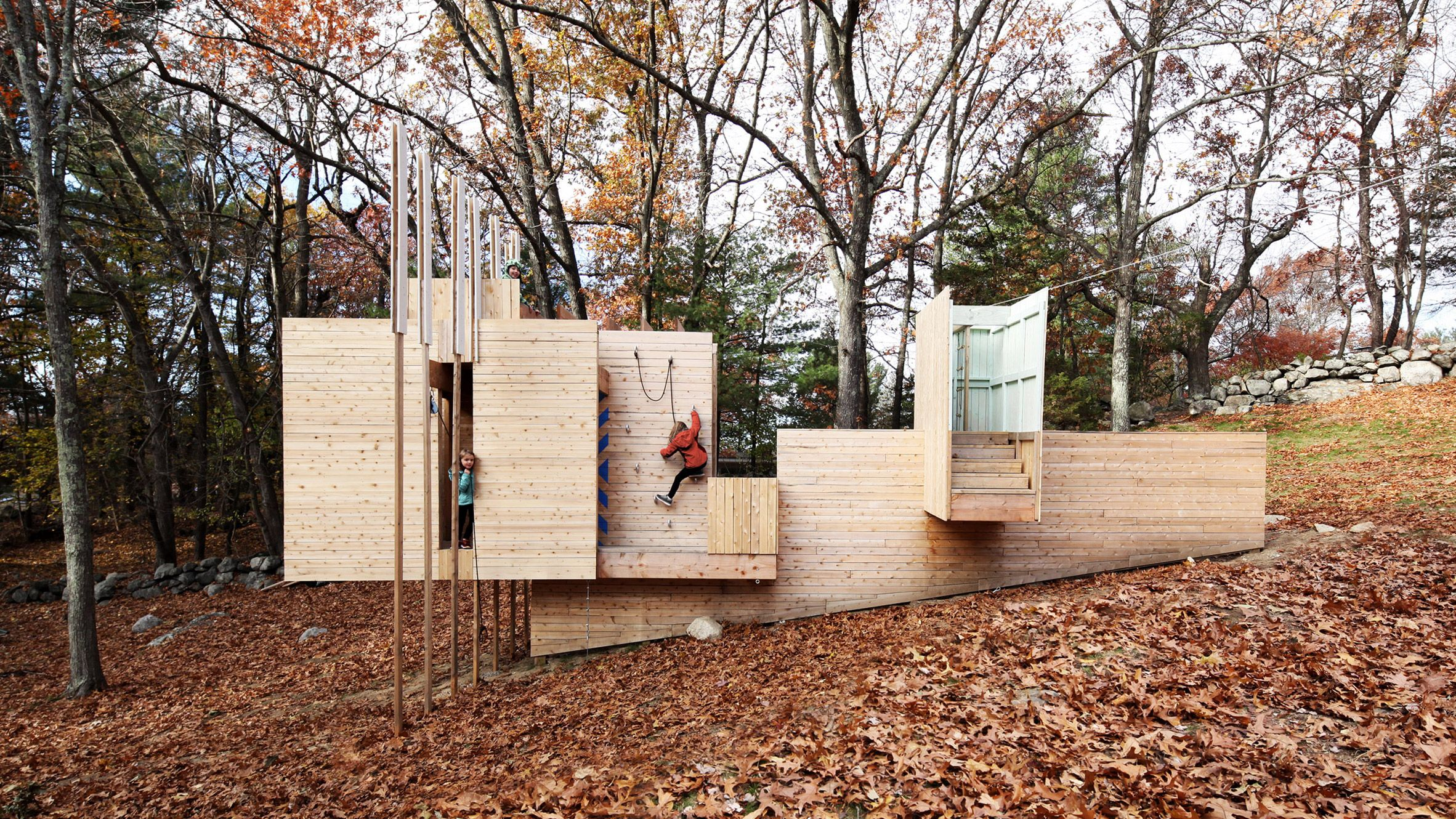 Intersecting wood-clad volumes create a playground for children in a Massachusetts suburb to scurry through, clamber over and zip-wire from.