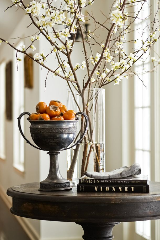 An autumnal entry table with fresh persimmons.