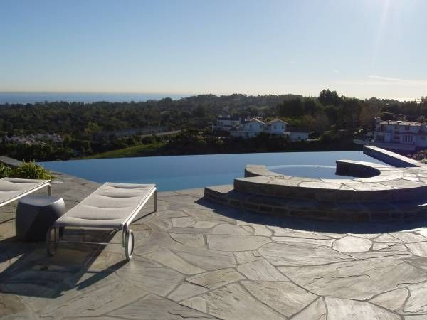 Vanishing edge pool with attached spa spilling into pool.