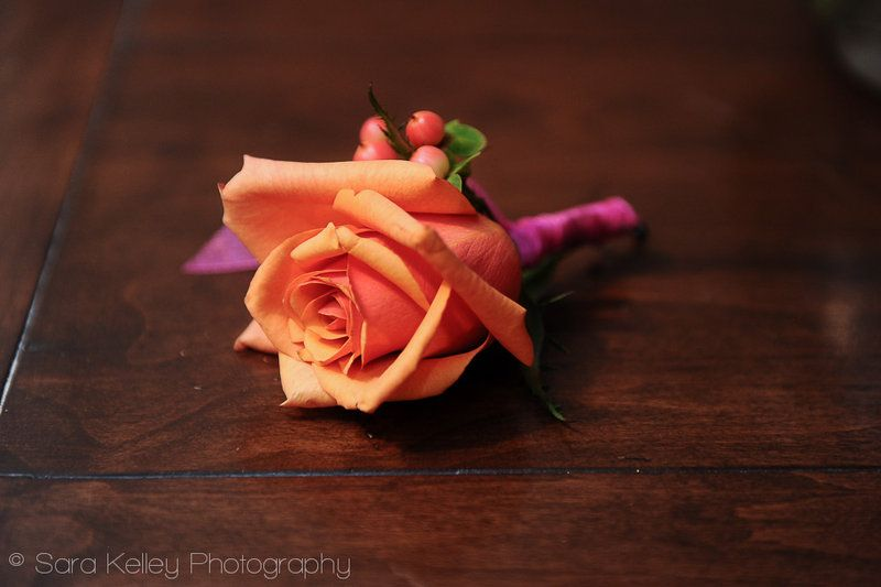 A bold orange rose boutonniere, finished with peach hypericum berries, and a hot pink silk ribbon, for an Indian Wedding, held at the Mercier Terrace room at the Ritz Carlton in New Orleans.