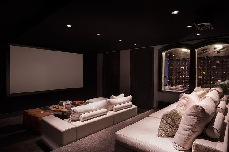 Black Movie Room Boasts Linen Theatre Seats And A Wood Coffee Table Colored Leather Poufs Facing Large Screen