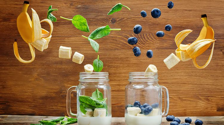 Two mason jars with bananas slicing themselves mid-air to fall into them along with herbs and blueberries