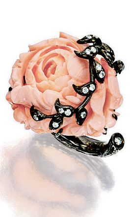 CORAL  AND DIAMOND RING   The ring modelled as a Peony, the flower head carved with coral measuring approximately 26.82 x 24.03 x 13.76 mm, embraced by pavé-set diamond leaves, to a stylised shank, mounted in 18 karat blackened gold.