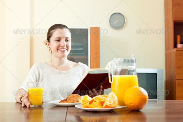 Young woman having breakfast ...  20s, 30s, Expressing, adult, book, breakfast, caucasian, cheerful, clock, croissant, domestic, drink, eat, eating, female, food, freshness, grass, happiness, home, house, indoors, interior, joy, juice, morning, one, orange, people, positivity, read, reading, relationship, room, smiling, table, woman, young