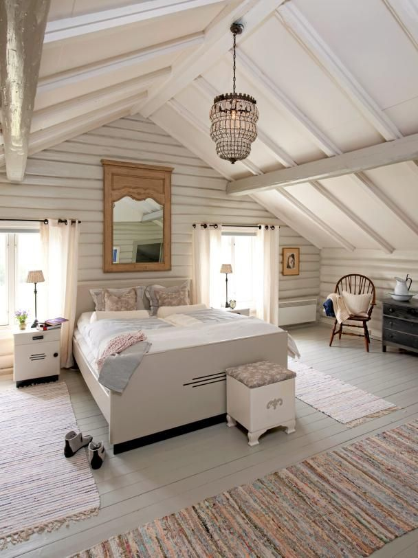 Cool calm white bedroom in cavernous beamed area accessorised in a modern casual way