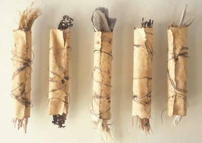 "Winter Pressings by Mary Ellen Long. These wrapped scroll forms hold gatherings found at the ""burial"" site.      ""Each year before the first snowfall, I lay paper of various sizes and forms on the earth. This paper becomes buried under the winter snows to then be harvested in the spring. This ritual documents the passage of time and the amount of snowfall that particular winter. This method is a little like printmaking with nature - the earth being the plate and the snow being the press."""