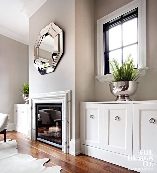 white built-ins, custom cabinetry, marble fireplace surround, mirror above fireplace, walnut floors, black windows