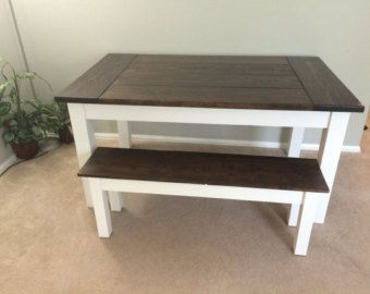 Plank table top with breadboard ends which makes this a very strong and sturdy table. This table has a dark walnut finish with tapered legs.