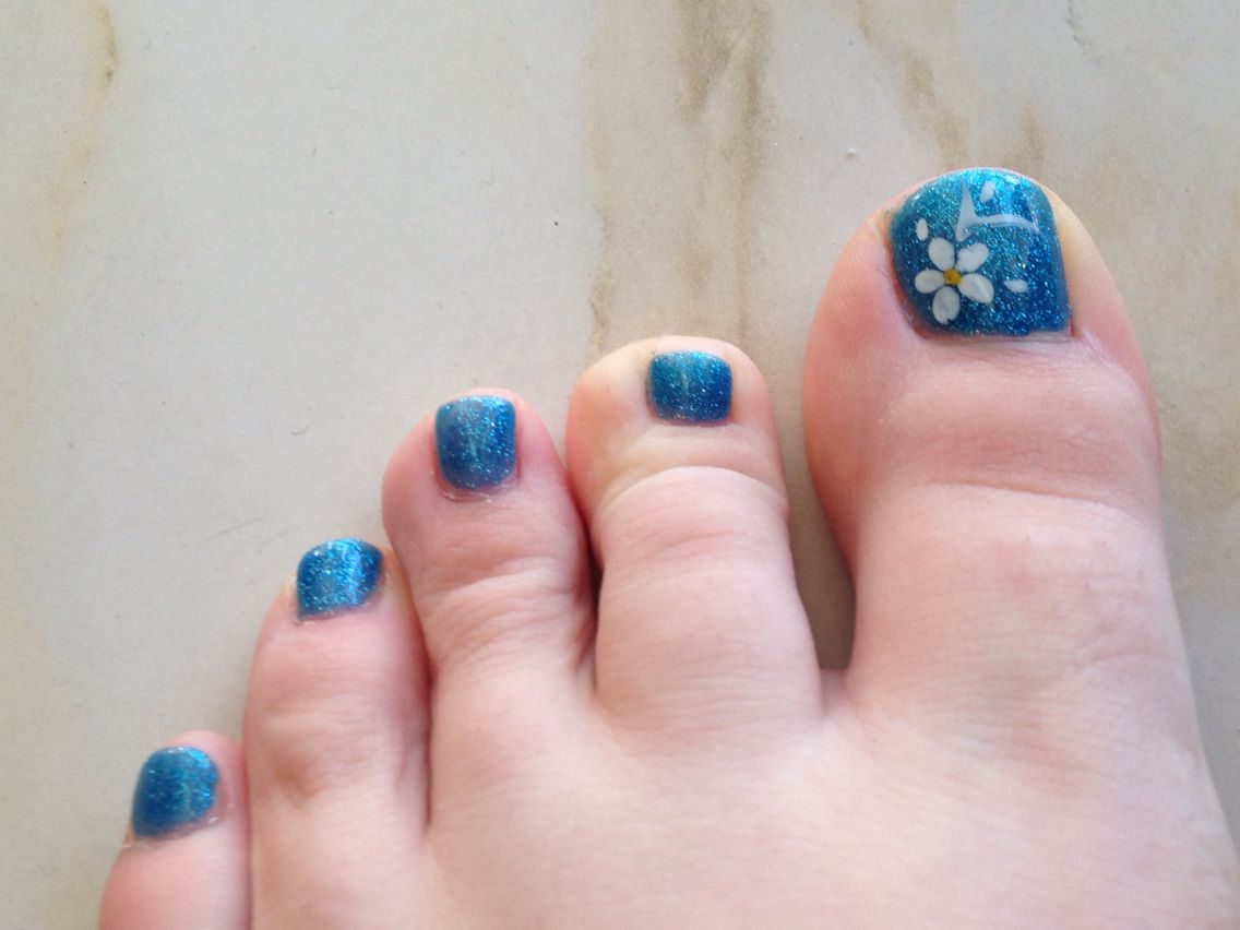 Spring time nails. Blue with sparkles. White flower.