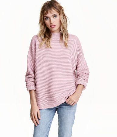 Pudderrosa. En strukturstrikket genser i myk kvalitet. Genseren er en vid modell med lange ermer og lav skuldersøm.