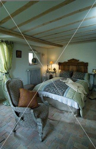 Einfaches Schlafzimmer mit Terrakottafliesen und niedriger Balkendecke; in der Mitte ein gemütliches Doppelbett mit rustikalem Kopfende aus Holz