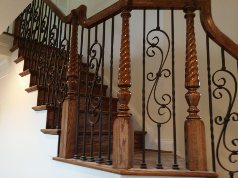 Stairway Landing Featuring Over The Post Style Stair Railing With Scroll  And Double Twist Iron Balusters