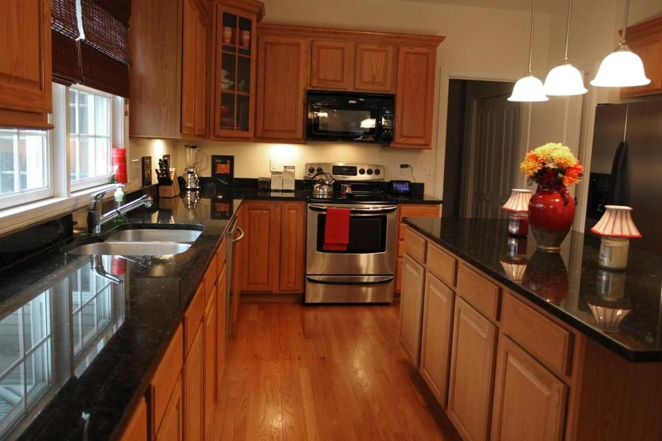 The kitchen features oak cabinets, dark granite counters ...