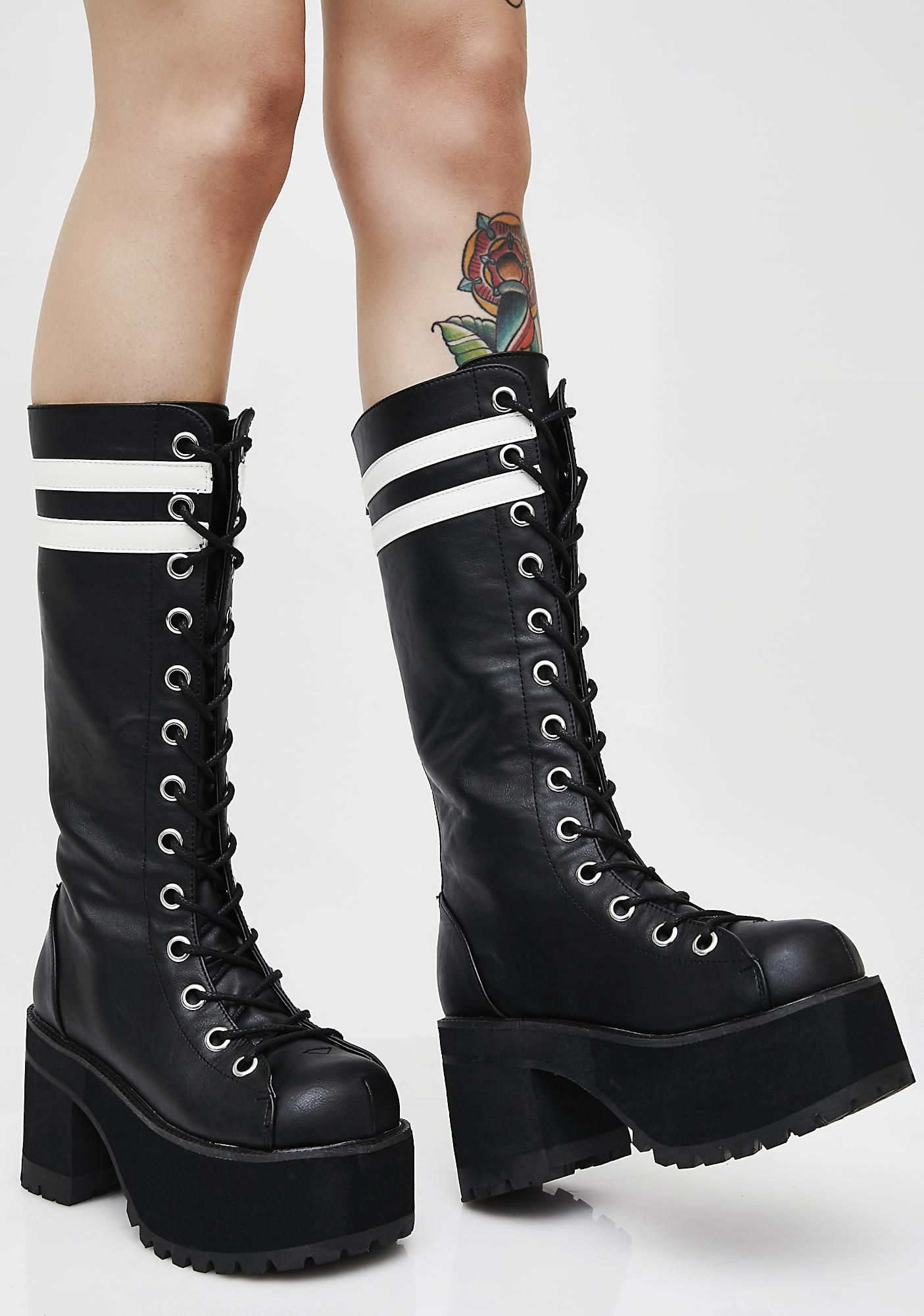 8baef3c29 These black boots have thick soles, lace-up fronts, back zipper closures,  and white stripes at the top.