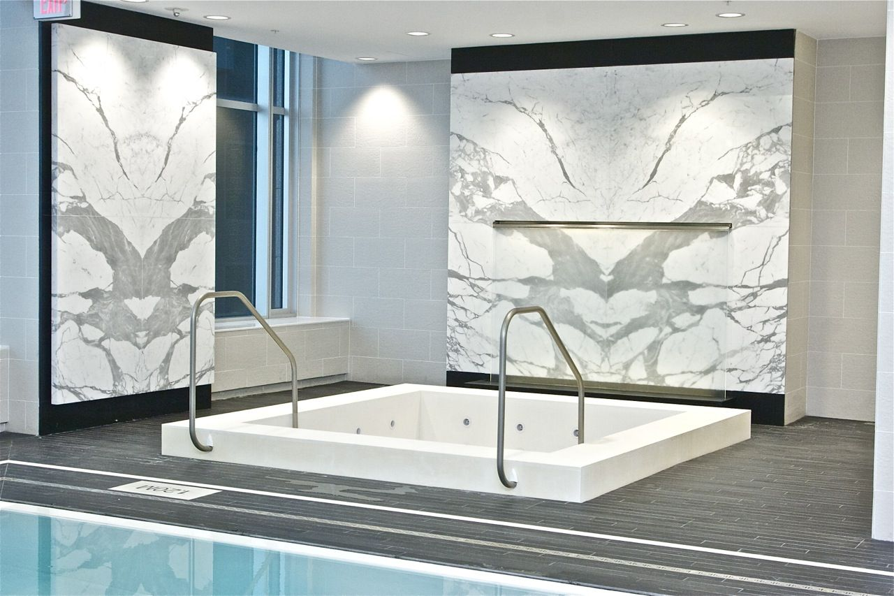book-matched statuario marble wall surrounding the whirlpool at