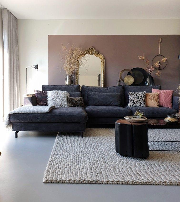 een zwarte, velours loungebank met fijne aardetinten er omheen