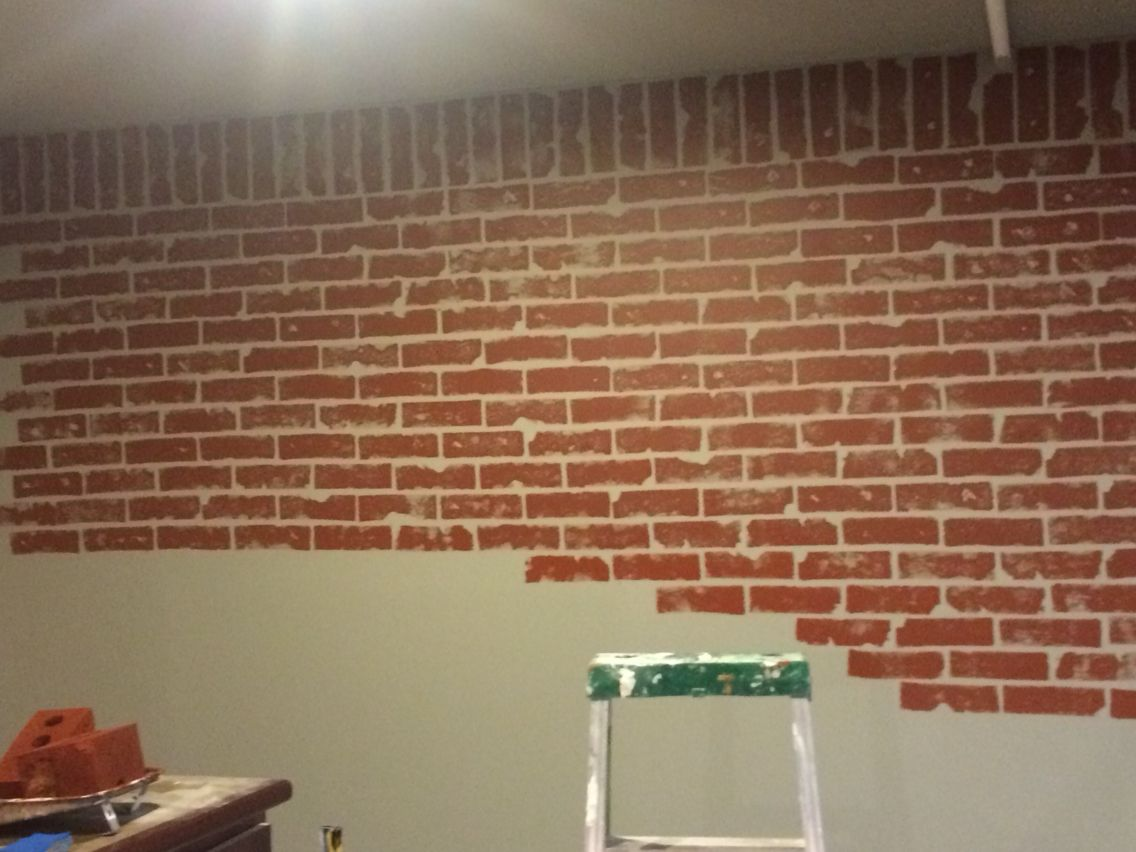 Faux brick wall in progress painted wall grey then used Grey sponge painted walls