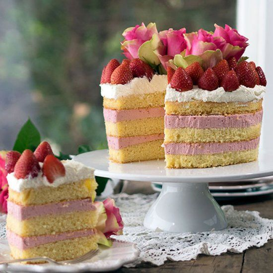 Strawberry Cheesecake Sponge Cake. Layers of fresh strawberry cheesecake between light as air sponge. Topped with cream & strawberries