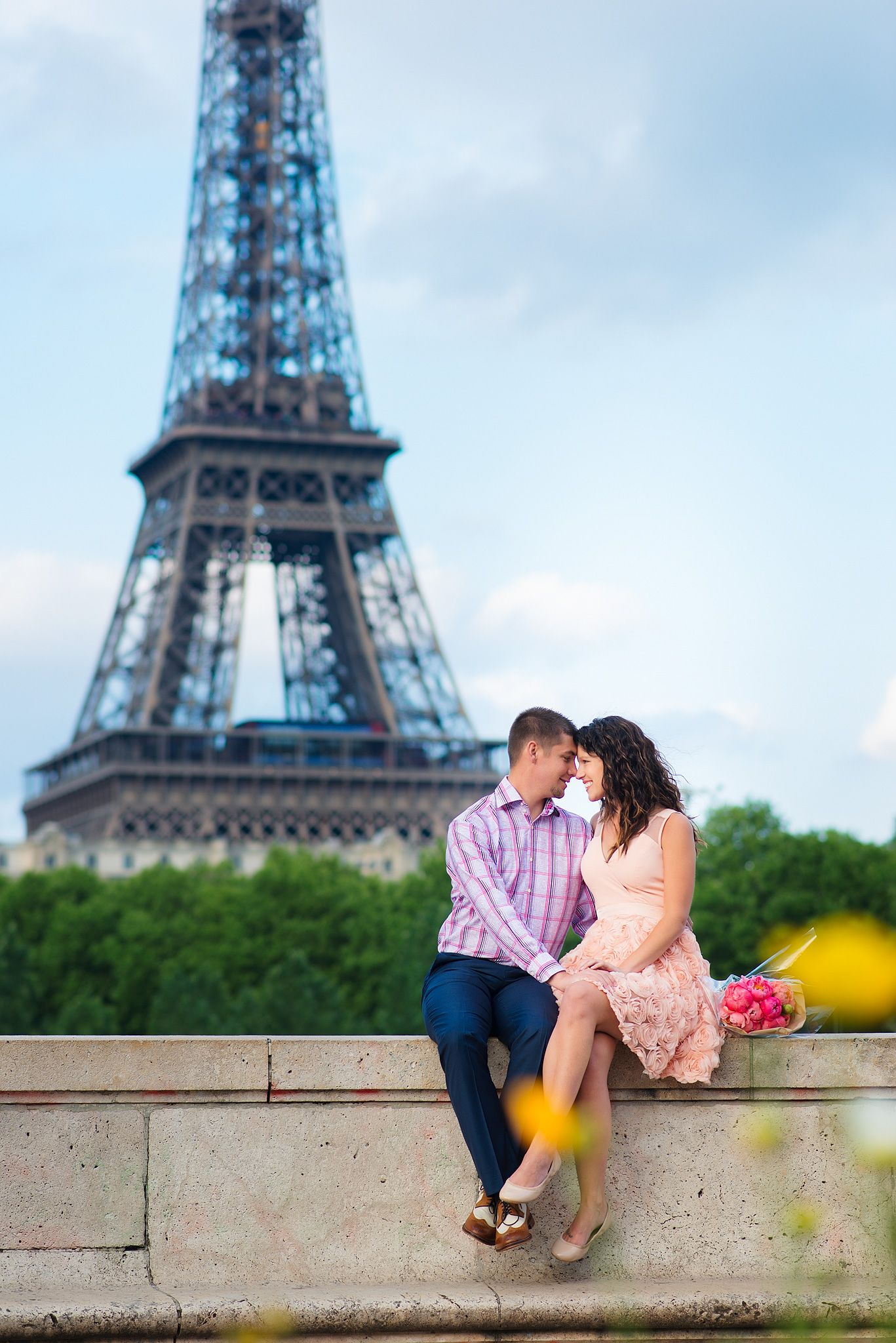cute couple in a romantic moment in front of the eiffel tower in paris beautiful pink peonies. Black Bedroom Furniture Sets. Home Design Ideas