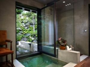 Concrete, steel, glass sunken tub with connection to outside water feature by Pinky and the Brain