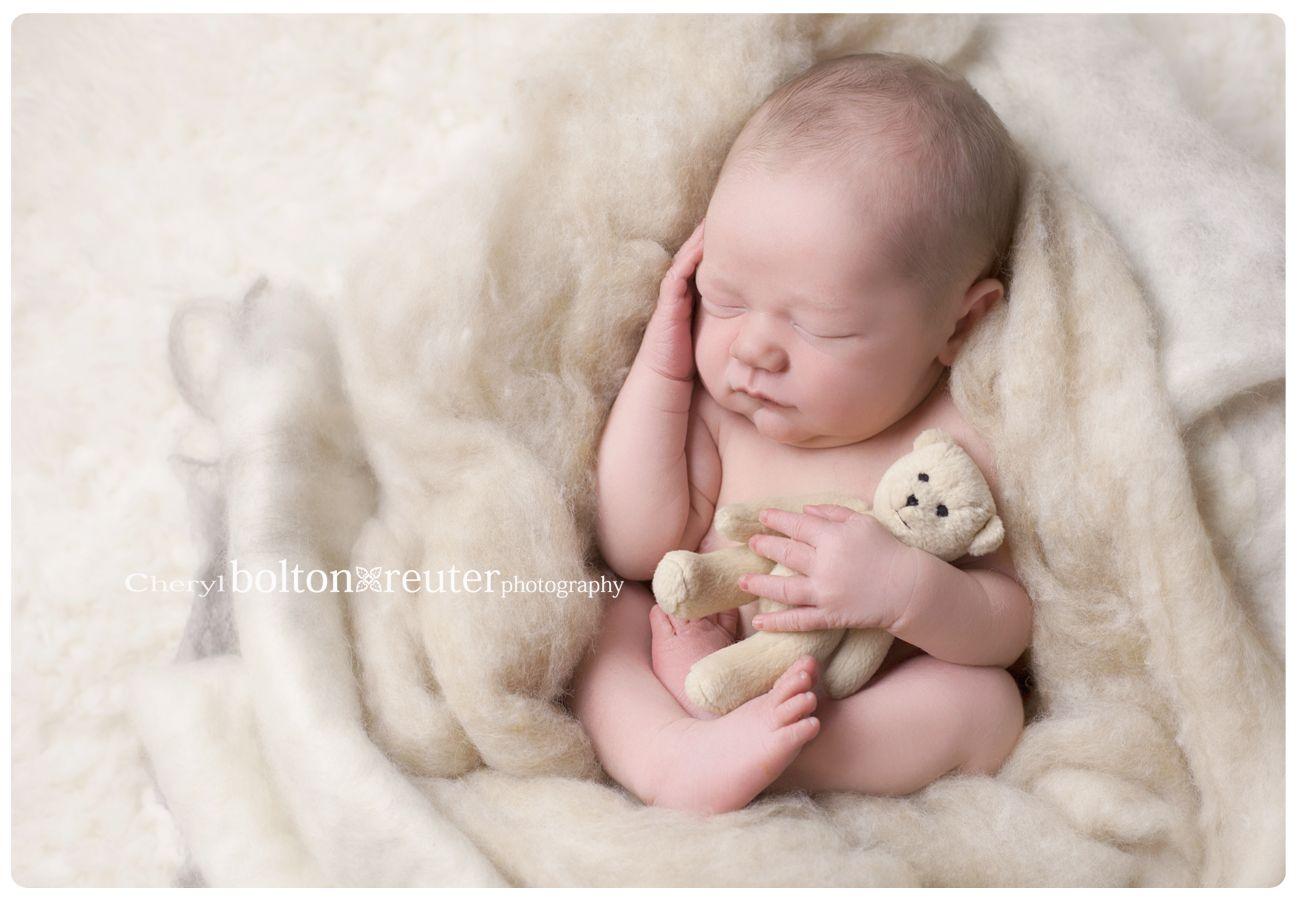 Newborn in wool fluff and teddy bear