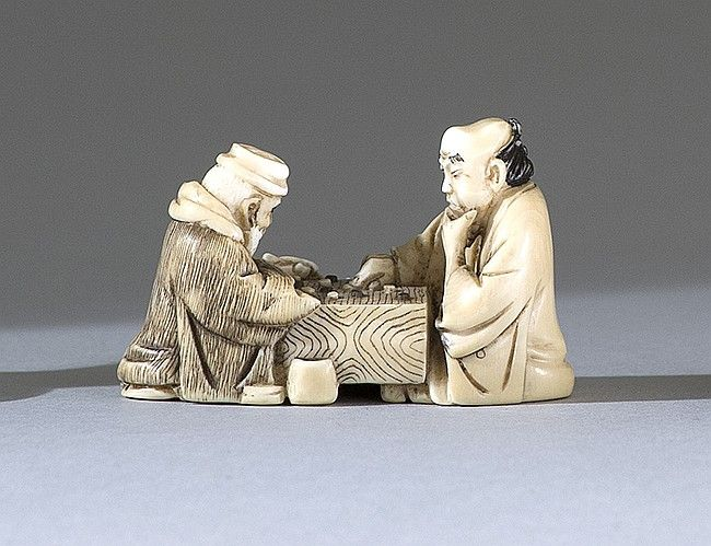 "IVORY NETSUKE Early 20th Century Depicting two sages playing Go. Signed on inlaid plaque. Length 2"" (5 cm)."