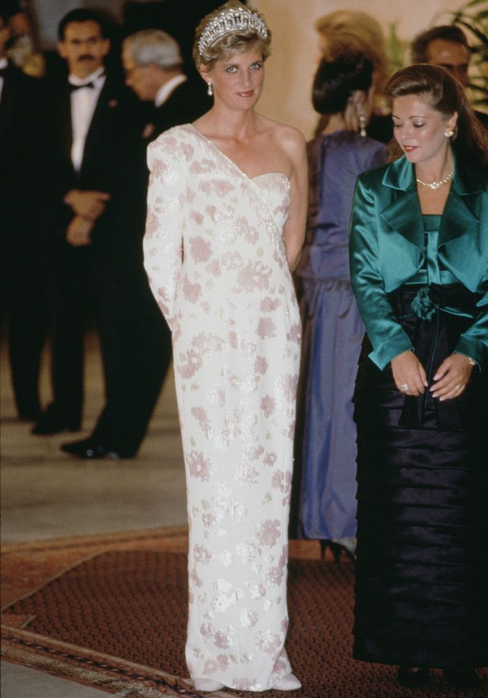 Princess Diana's Iconic Outfits  ~~ Princess Diana The Princess of Wales wears a stunning one-shoulder white and silver gown designed by Catherine Walker. We wish we could wear massive tiaras too.